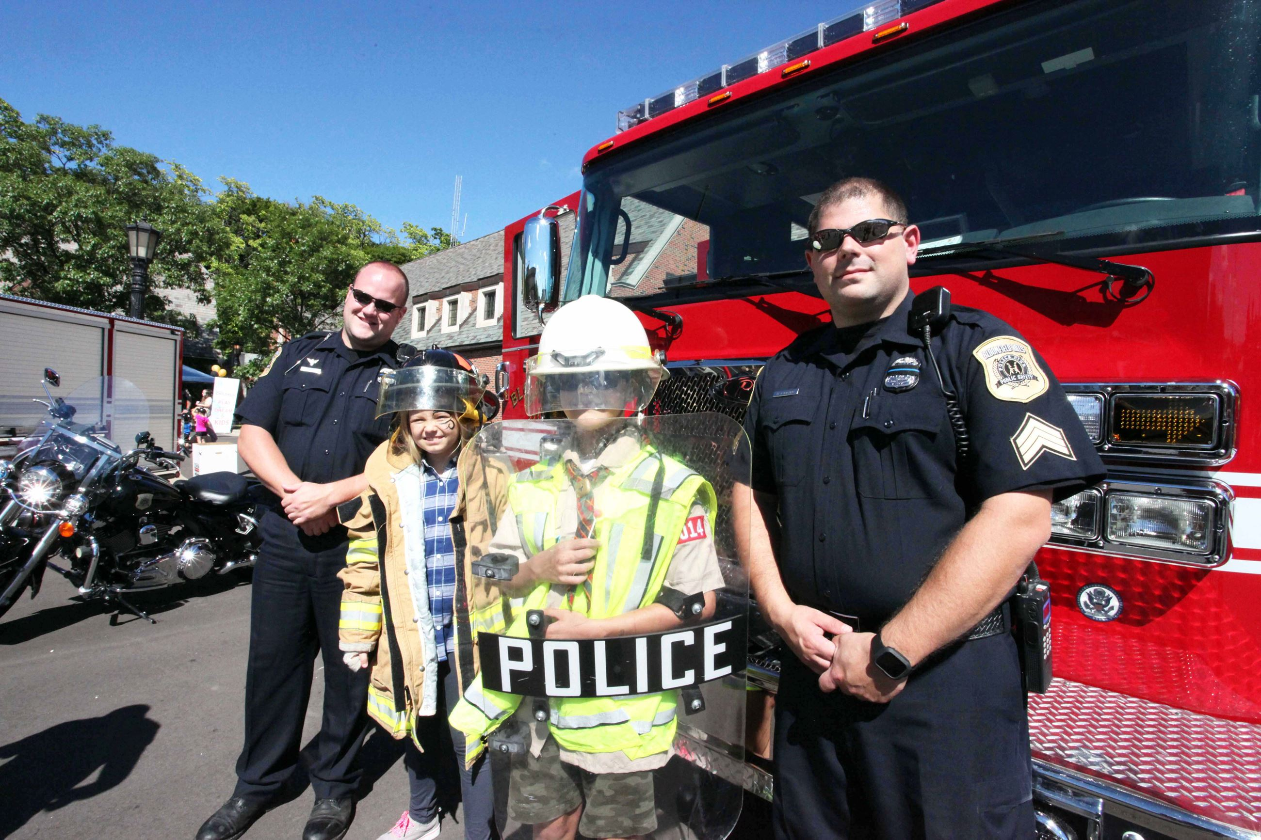 Kids Posing in Police and Fire Gear with Officers
